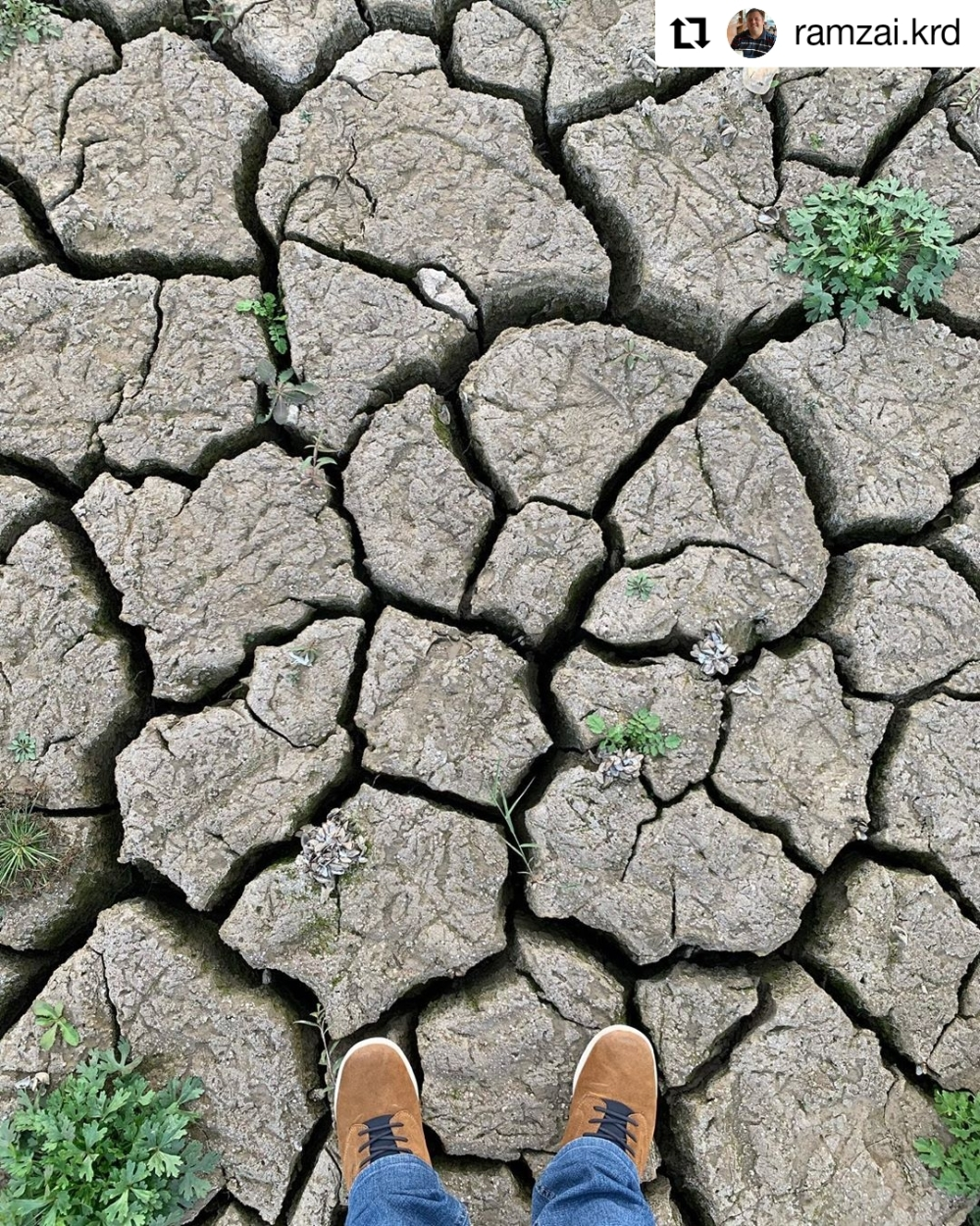 dried out earth with a pair of feet standing on it